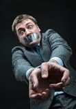 Man with mouth covered by masking tape. Man with mouth and hands  covered by masking tape, studio shoot Royalty Free Stock Photos