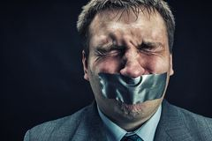 Man with mouth covered by masking tape. Preventing speech, isolated on black Royalty Free Stock Image