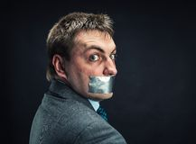 Man with mouth covered by masking tape. Studio shoot Stock Photography