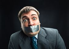 Man with mouth covered by masking tape. Surprised man with mouth covered by masking tape preventing speech, studio shoot Royalty Free Stock Photo