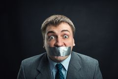 Man with mouth covered by masking tape. Young man with mouth covered by masking tape preventing speech, studio shoot Royalty Free Stock Photo