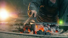 A man moves coal in fire, working at a forge. 4K stock video