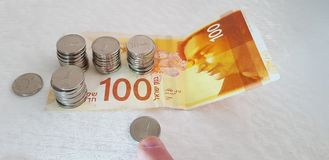 Man moves one israeli sheckel coin with his finger towards new 100 shekels banknote stock photo