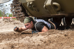 Man moves under tank in extrim race. Tyumen Royalty Free Stock Images