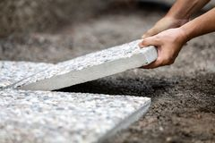 Man moves washed concrete slabs into a gravel bed stock photography
