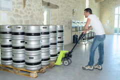 Man moving barrels beer with pallet truck. Man moving barrels of beer with pallet truck Royalty Free Stock Photography