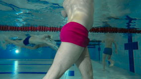 The man moving the body underwater in swimming pool. Underwater shooting. The man standing in the swimming pool and moving his body in different sides. The man stock video footage