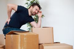 Man feeling back ache cramp moving heavy boxes. Man moving boxes and feeling back pain because heavy weight Royalty Free Stock Photo