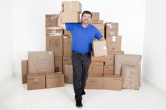 Man moving boxes. Man picking up moving boxes with more boxes stacked behind him Royalty Free Stock Photography