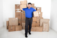 Man moving boxes. Man picking up moving boxes with more boxes stacked behind him Stock Photography