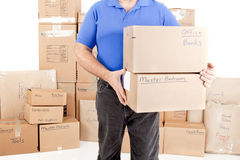 Man moving boxes. Man picking up moving boxes with more boxes stacked behind him Royalty Free Stock Image