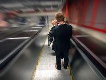 Man in moving escalator. Man standing on descending escalators, photographed from the back, motion Stock Photos
