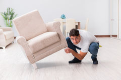 The man moving furniture at home Stock Images