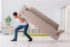 The man moving furniture at home Stock Image