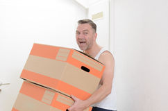 Man moving home carrying cardboard cartons Royalty Free Stock Images
