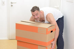 Man moving home carrying cardboard cartons Royalty Free Stock Photos