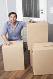 Man moving house. Man with cartoon boxes in apartment Stock Image