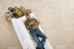 Man moving house, lying on white sofa, taking tea break, smiling, portrait, overhead view Royalty Free Stock Images