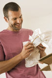 Man moving house, wrapping crockery in paper, smiling, close-up Royalty Free Stock Image