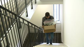 Man Moving Into New Home Carrying Box Upstairs. Man carrying boxes up stairs as they move into new home.Shot on Sony FS700 in PAL format at a frame rate of 25fps stock video