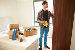Man Moving Into New Home And Unpacking Boxes In Bedroom. Putting Clothes Into Wardrobe stock image