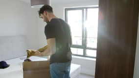 Man Moving Into New Home Unpacking Clothes In Bedroom stock footage