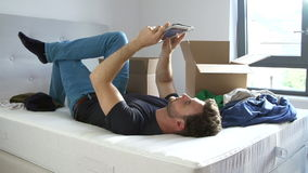 Man Moving Into New Home Using Digital Tablet Lying On Bed Royalty Free Stock Photo