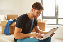 Man Moving Into New Home Using Laptop Computer
