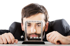 Man moving newton balls in office. Businessman moving newton balls in office Stock Photo