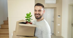 Man Moving to New Home. Handsome smiling man holding cardboard box and smiling to camera, moving to new home, portrait stock video