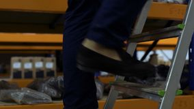 Man moving up the ladder. At storage. Close-up stock video footage