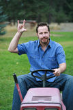 Man on mower rocking out. Man on riding lawn mower, rocking out, having a good time Stock Photo