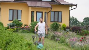 Man mowing garden lawn with mower machine in yard