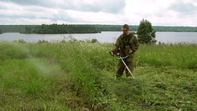 A man mowing the grass trimmer. Work in the village stock video