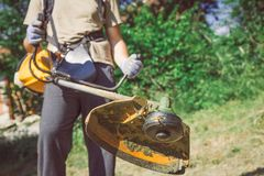 Close up of man using string trimmer for cutting grass in the ga. Man Mowing the Grass by using gasoline lawn trimmer Stock Photography