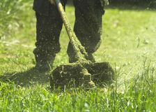 The man mowing green wild grass field using brush cutter mower or power tool string lawn trimmer. To mow a grass with the trimmer. Trimer mows a lawn. Care of stock photos