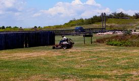 Man Mowing Large Area Next to Beach Park stock images