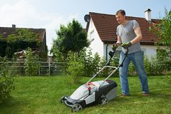Man mowing lawn in backyard. Man cutting grass in his garden yard with lawn mower Royalty Free Stock Photos