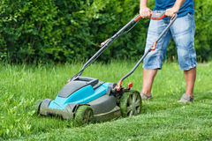 Man mowing the lawn with blue lawnmower in summertime Stock Photos