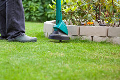 Man mowing lawn with grass trimmer Royalty Free Stock Images