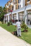 Man mowing lawn in a hotel garden Stock Photos