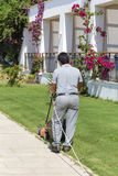 Man mowing lawn in a hotel garden Royalty Free Stock Images