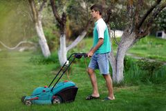 Man mowing the lawn with lawnmower Stock Photos