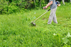 Man mowing lawn mower green, young grass. Gardener doing seasonal work. Clearing the garden of weeds Royalty Free Stock Photo