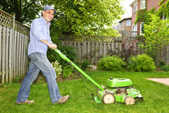 Man mowing lawn. Man with lawn mower in landscaped backyard stock image