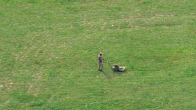 A man mows the grass with a lawnmower on a large meadow. stock video footage