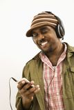 Man with mp3 player. African-American mid-adult man wearing knit hat and listening to headphones and mp3 player Royalty Free Stock Photos