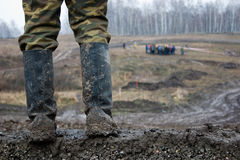 The man in muddy kersey boots. The man stand  in muddy kersey boots Royalty Free Stock Photography