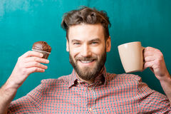 Man with muffin and coffee Stock Images