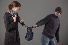 Man mugging woman Stock Images